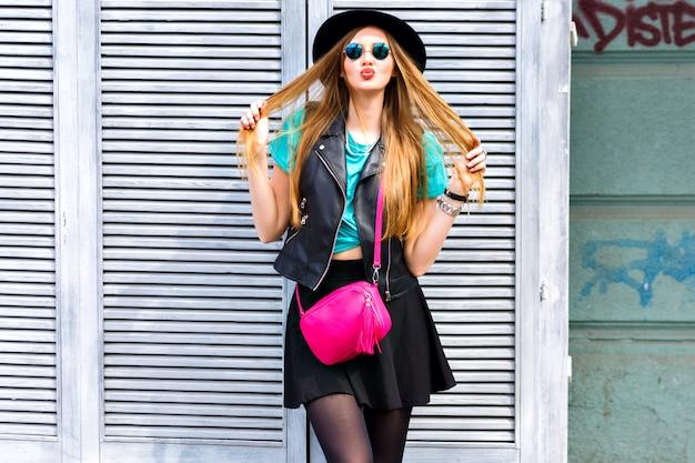 Mulher loira sexy elegante posando na rua, vestindo roupa brilhante hipster, emoções legais lúdicas, diversão, divirta-se, férias felizes sozinha, chapéu vintage e minissaia. Foto gratuita