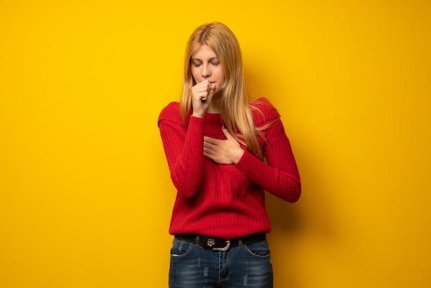 Mulher loira sobre parede amarela está sofrendo com tosse e se sentindo mal Foto Premium