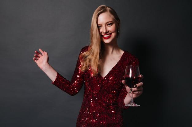 Mulher loira sorridente bebendo vinho tinto. foto de estúdio de menina bonita em vestido de dança em fundo preto. Foto gratuita