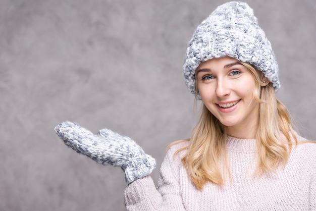 Mulher loira sorridente com luvas Foto gratuita