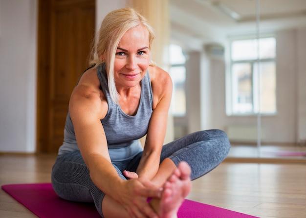 Mulher loira sorridente fazendo pilates Foto gratuita