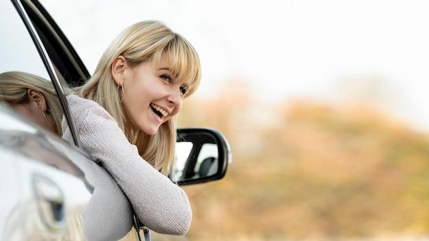 Mulher loira sorridente, levando a cabeça para fora do carro de janela Foto gratuita