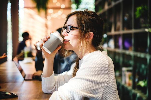 Mulher loira tomando uma xícara de café Foto gratuita