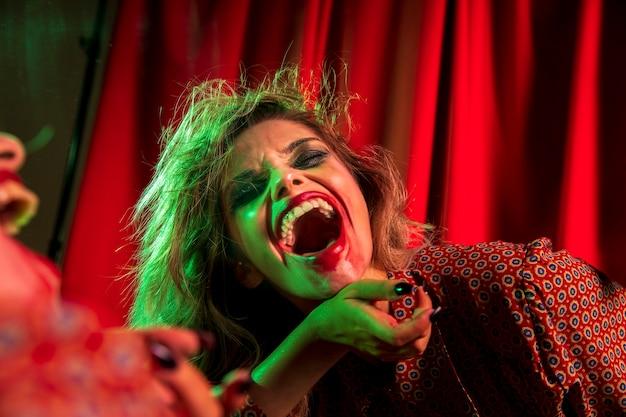 Mulher louca de palhaço de halloween rindo Foto gratuita