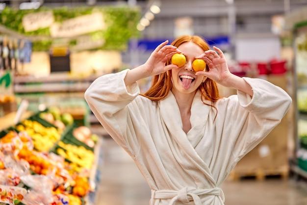 Mulher louca de roupão se divertindo com tangerinas, segurando mandarinas nos olhos, no supermercado, mostrando a língua Foto Premium