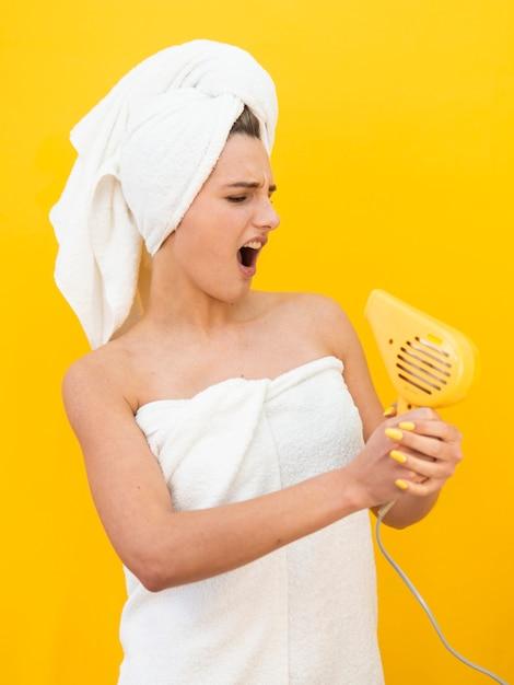 Mulher louca segurando o secador de cabelo Foto gratuita