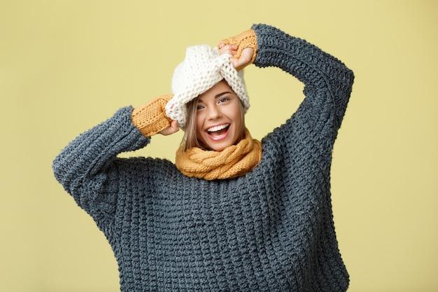 Mulher loura bonita engraçada nova no lenço da camisola do chapéu knited e nas luvas que sorriem no amarelo. Foto gratuita