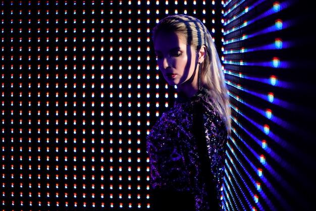 Mulher loura bonita no fato na moda que aprecia a vida noturno, menina lindo dentro na iluminação de néon. Foto Premium