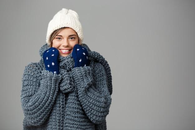 Mulher loura bonita nova na camisola knited do chapéu e luvas que sorriem no cinza. Foto gratuita