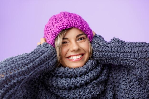 Mulher loura bonita nova no chapéu e na camisola knited que sorriem na violeta. Foto gratuita