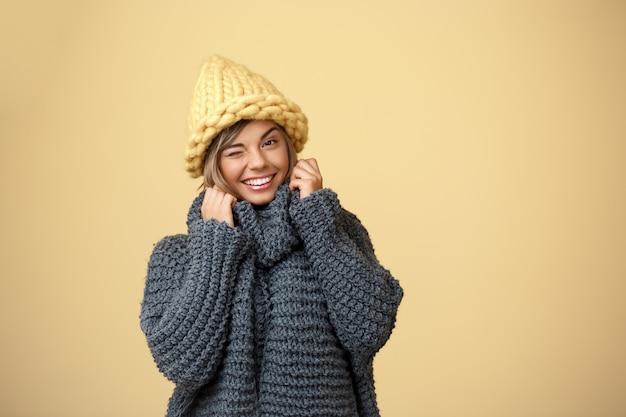 Mulher loura bonita nova no chapéu e na camisola knited que sorriem piscando no amarelo. Foto gratuita