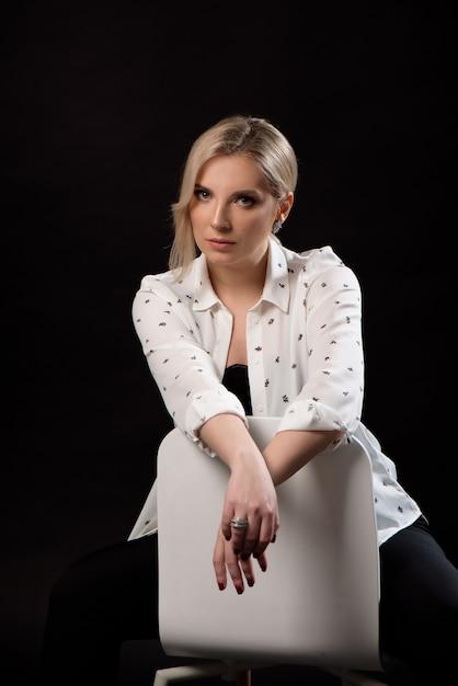 Mulher loura bonita nova que senta-se em uma cadeira no estúdio no fundo preto Foto Premium