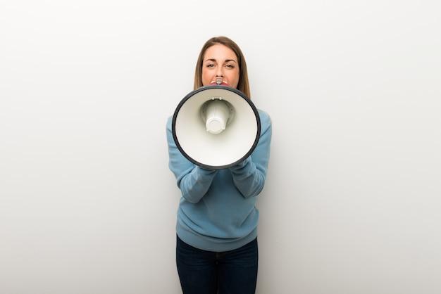 Mulher loura no fundo branco isolado que shouting através de um megafone para anunciar algo Foto Premium