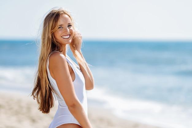 Mulher loura nova com corpo bonito no roupa de banho branco em uma praia tropical. Foto gratuita
