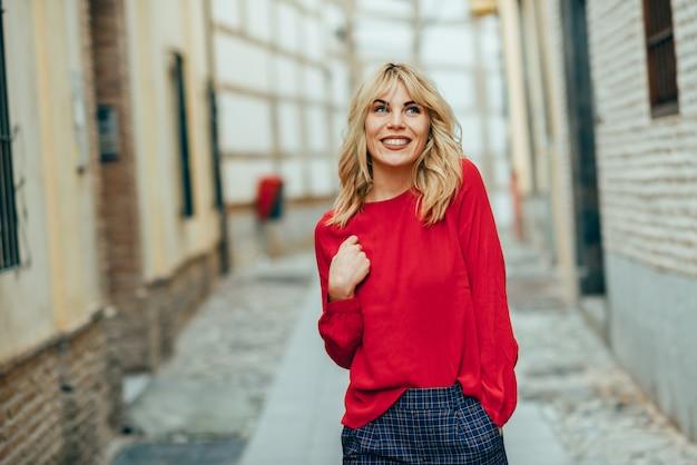 Mulher loura nova feliz que anda abaixo da rua. Foto Premium