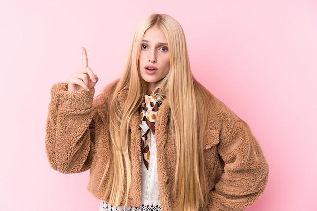 Mulher loura nova que veste um casaco contra um fundo cor-de-rosa que tem uma ideia, conceito da inspiração. Foto Premium