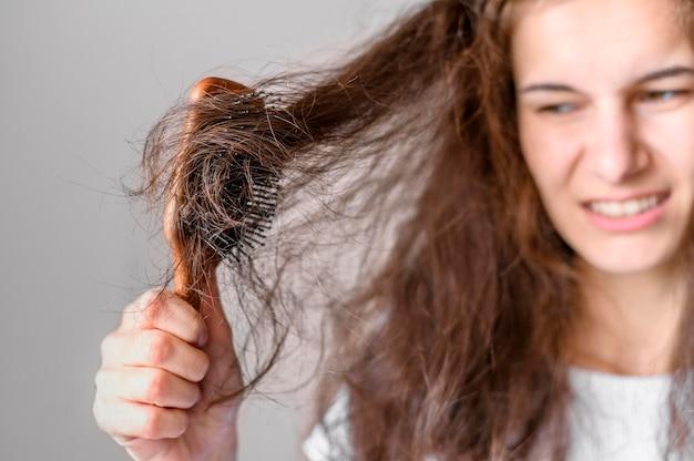 Mulher lutando para escovar o cabelo Foto gratuita