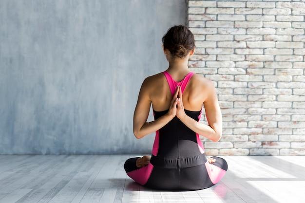 Mulher, maditating, com, mãos dobraram, em, namaste, ioga posa Foto gratuita