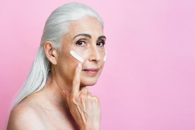 Mulher madura, aplicar creme no rosto Foto gratuita