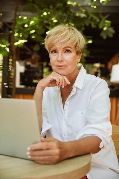 Mulher madura atraente, sentado em um café com laptop Foto Premium