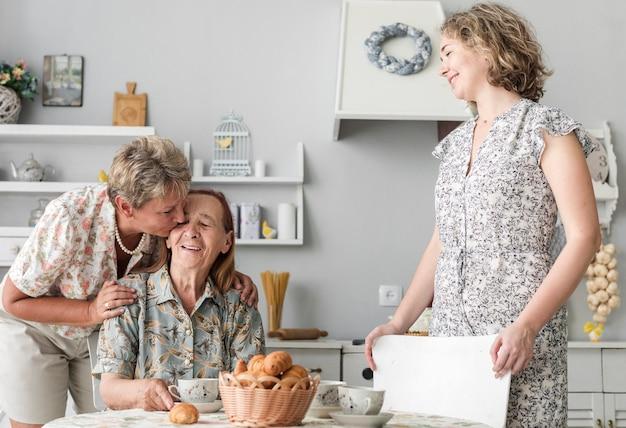 Mulher madura, beijando, dela, mãe sênior, em, cozinha Foto gratuita