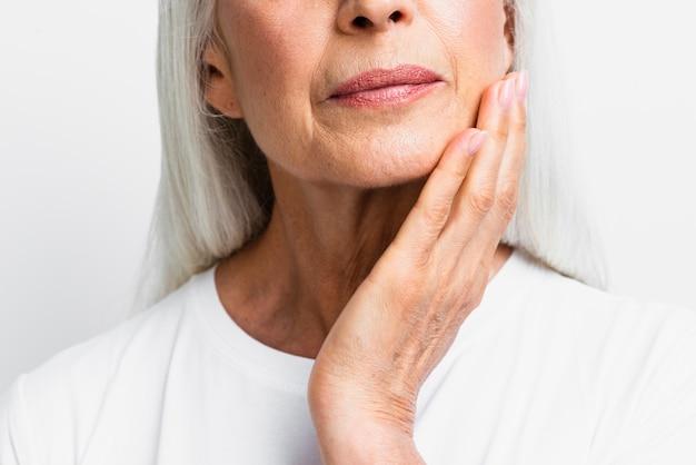 Mulher madura close-up, aplicando cuidados com a pele Foto gratuita