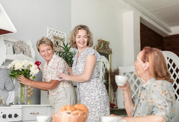 Mulher madura, com, filha, organizando, flores, vaso, ligado, contador cozinha, enquanto, dela, mãe, comendo café Foto gratuita