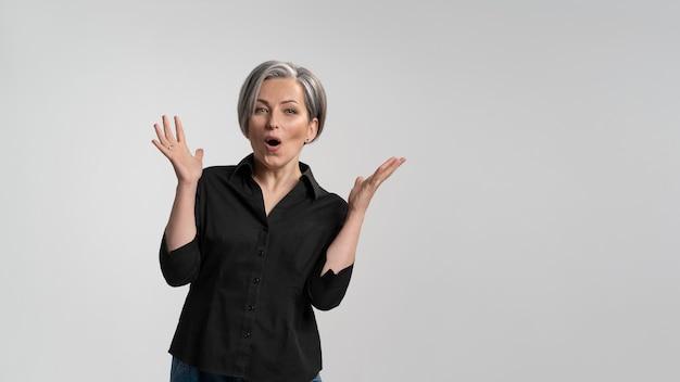 Mulher madura de cabelos grisalhos fazendo um gesto de espanto. mulher bonita de cabelos grisalhos de meia-idade em camisa preta Foto Premium