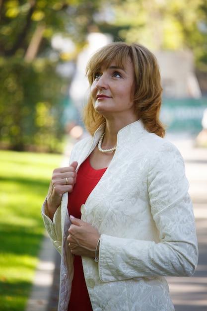 Mulher madura de meia-idade, olhando pensativamente para uma caminhada no parque Foto Premium