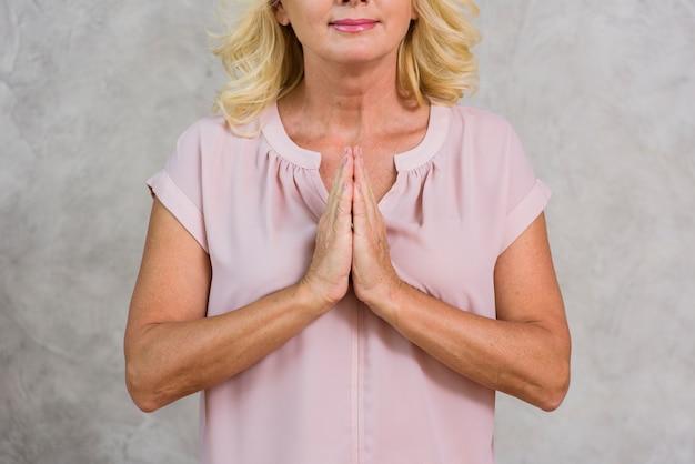 Mulher madura de vista frontal rezando | Foto Grátis