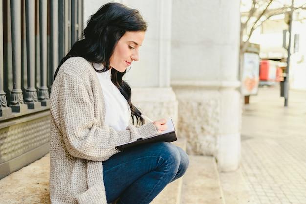 Mulher madura do retrato que toma notas em seu caderno, apontando seus sonhos e planos futuros. Foto Premium
