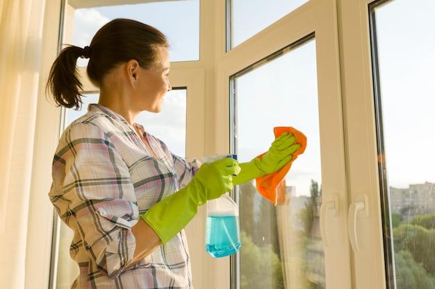 Mulher madura em casa lavando a janela Foto Premium