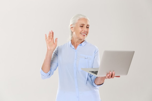 Mulher madura engraçada usando computador portátil isolado sobre o branco Foto gratuita