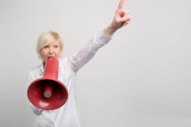 Mulher madura está segurando um megafone perto da boca e gritando nele. ela está defendendo os direitos humanos. Foto Premium