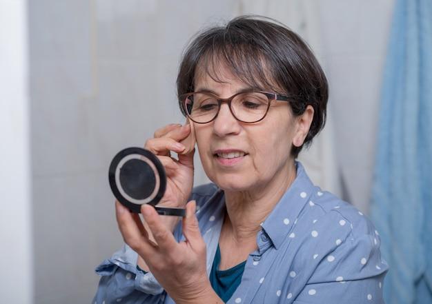 Mulher madura, fazendo, maquilagem, enquanto, olhar, pequeno, espelho Foto Premium