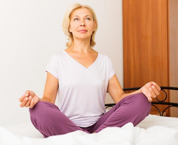 Mulher madura fazendo yoga na cama | Foto Premium