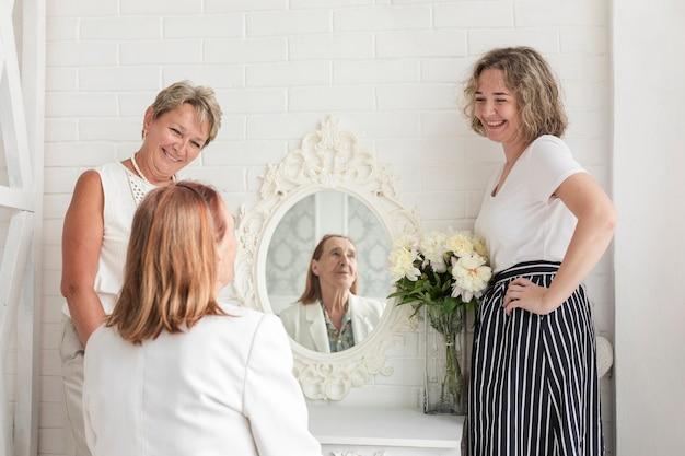 Mulher madura, ficar, com, filha, olhar, dela, mãe sênior, sentando, frente, espelho Foto gratuita