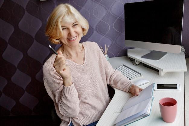 Mulher madura loira sorridente, escrevendo em seu planejador enquanto trabalhava pelo computador em casa Foto gratuita