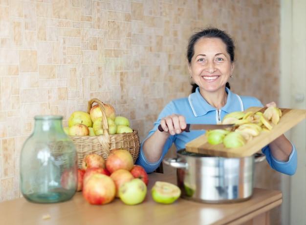 Mulher madura que cozinha geléia de maçã Foto gratuita
