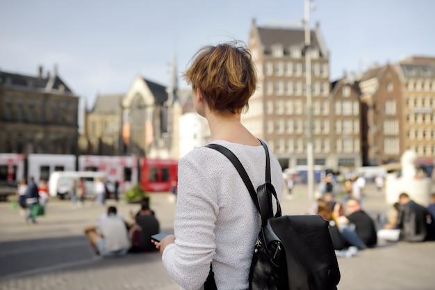 Mulher madura que está em um dia ensolarado do outono no quadrado central da represa na cidade velha de amsterdão. turismo e viagens. Foto Premium