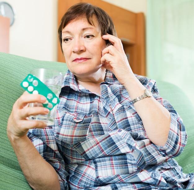 Mulher madura séria com pílulas e copo de água Foto gratuita