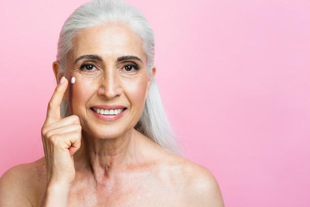 Mulher madura sorridente, aplicar creme hidratante Foto gratuita