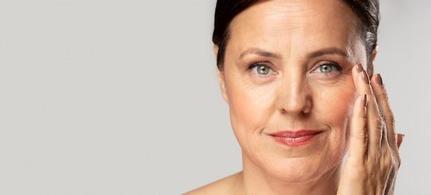 Mulher madura sorridente com maquiagem, posando com a mão no rosto e copie o espaço Foto Premium