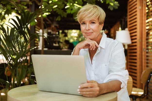 Mulher madura sorridente, sentado em um café com laptop Foto Premium