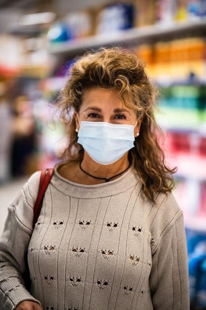 Mulher madura sorrindo para a câmera enquanto usa máscara no supermercado Foto Premium
