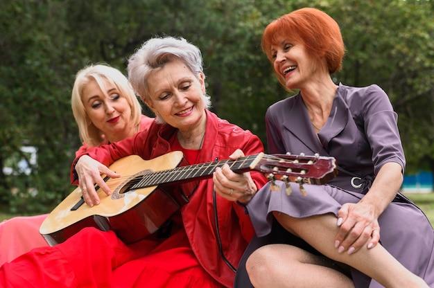 Mulher madura, violão jogo, com, amigos Foto gratuita