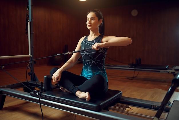 Mulher magra em roupas esportivas, treinamento de pilates Foto Premium
