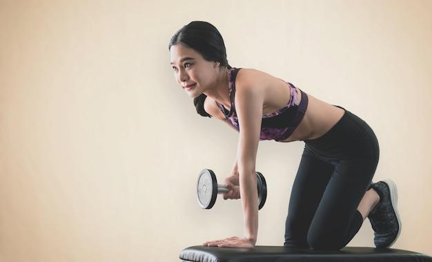 Mulher magro asiática forte está levantando halteres em fitness Foto Premium