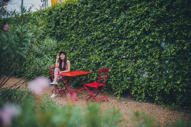 Mulher mais jovem asiática, sentado no parque verde Foto Premium