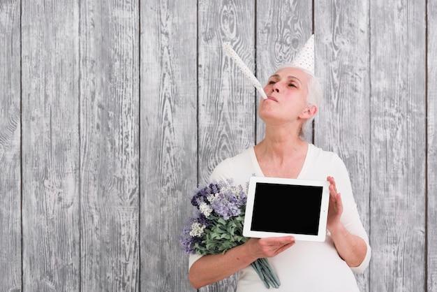 Mulher mais velha alegre soprando festa chifre segurando o tablet digital e buquê de flores roxas na mão Foto gratuita